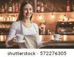 beautiful female barista is... | Shutterstock . vector #572276305