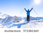 back view of a happy skier with ... | Shutterstock . vector #572381365
