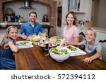 happy family having meal in... | Shutterstock . vector #572394112
