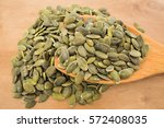 squash seeds on wooden spoon... | Shutterstock . vector #572408035