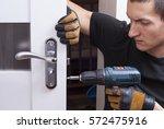 handyman repair the door lock... | Shutterstock . vector #572475916