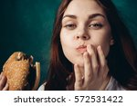 joyful woman holding a burger... | Shutterstock . vector #572531422