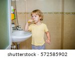 a toddler brushing his teeth in ... | Shutterstock . vector #572585902