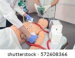 cpr training using medical dummy | Shutterstock . vector #572608366