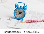 alarm clock  pen and tax forms   | Shutterstock . vector #572684512