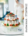 Small photo of Bide stands behind delicious wedding cake decorated with red berries and dark chocolate