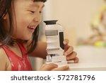 girl using microscope at home... | Shutterstock . vector #572781796