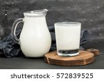 glass and jar milk on wooden... | Shutterstock . vector #572839525