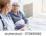 doctor questioning pensioner in ... | Shutterstock . vector #572850082