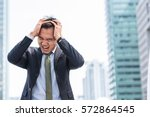 Stock photo stressed asian businessman scream while cover his head with both hands with city in background 572864545