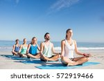 people doing yoga on the beach...   Shutterstock . vector #572919466