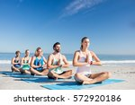 people doing yoga on the beach...   Shutterstock . vector #572920186