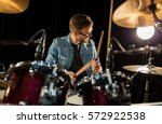 Small photo of music, people, musical instruments and entertainment concept - male musician with drumsticks playing drums and cymbals at concert or studio