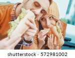 couple eating sandwich and... | Shutterstock . vector #572981002