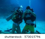 young couple on the seafloor... | Shutterstock . vector #573015796