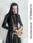 Small photo of Magic Wizard With Albino Snake Wearing Black Stylish Leather Coat with Golden Chains