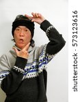 Small photo of rapper dancing looking cool in gangsta rap headband . ethnic asian fashion singer posing with hands framing oriental face on neutral background.