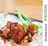 Small photo of Nylon-Tong is holding tandoori chicken on aluminium foil