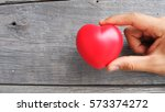 giving a red heart on wood... | Shutterstock . vector #573374272