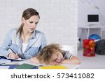 bored child lying with head on... | Shutterstock . vector #573411082