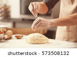 Small photo of Man sprinkling flour over fresh dough on kitchen table