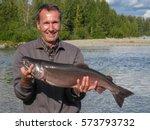 Angler showing his catch, a silver salmon, Talkeetna River, Alaska