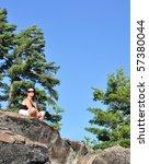 Woman meditating under a pine tree - stock photo