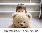 kid hugging teddy bear indoor... | Shutterstock . vector #573822052