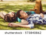 couple relaxing together in park | Shutterstock . vector #573840862