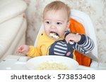 little baby boy eating sitting... | Shutterstock . vector #573853408