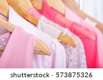 Stock photo pink womens clothes on hangers on rack in fashion store closet 573875326