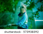 woman is watering the trees in... | Shutterstock . vector #573938392