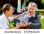 nurse holding hands with senior ... | Shutterstock . vector #573963625