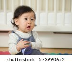 cute baby girl holding sip cup | Shutterstock . vector #573990652