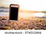 smart phone on tropical sunset... | Shutterstock . vector #574012846