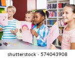 kids showing drawing in library ... | Shutterstock . vector #574043908