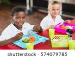 Stock photo portrait of boy and girl in school uniforms having lunch in school cafeteria 574079785