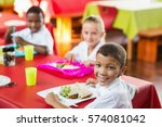 Stock photo happy children having lunch during break time in school cafeteria 574081042