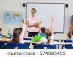 pupils with hands up during... | Shutterstock . vector #574085452