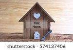 Small photo of Conceptual image of miniature home icon made from wood and word written FIRST HOME on wooden base.Selective focus.