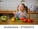 little girl eating broccoli.... | Shutterstock . vector #574303372