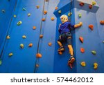 little boy climbing wall in... | Shutterstock . vector #574462012