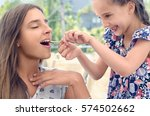 Small photo of Smiling girl is feeding her sister with spoon. Guess taste. Tasting sour lemon juice.