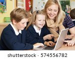 teacher helping elementary... | Shutterstock . vector #574556782