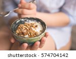 young woman with muesli bowl.... | Shutterstock . vector #574704142