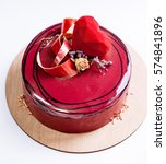 Small photo of Trendy mousse cake covered with red mirror glaze. Velour chocolate heart and dry rose decor. White background.