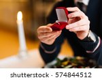 male hands with red velvet box... | Shutterstock . vector #574844512