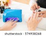 female hands using portable uv...   Shutterstock . vector #574938268