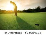 golfer putting golf ball on the ... | Shutterstock . vector #575004136