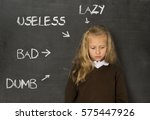 Small photo of little beautiful blond schoolgirl sad ashamed and embarrassed being pointed and marked on school class blackboard with the words lazy useless bad and dumb in abuse discipline concept